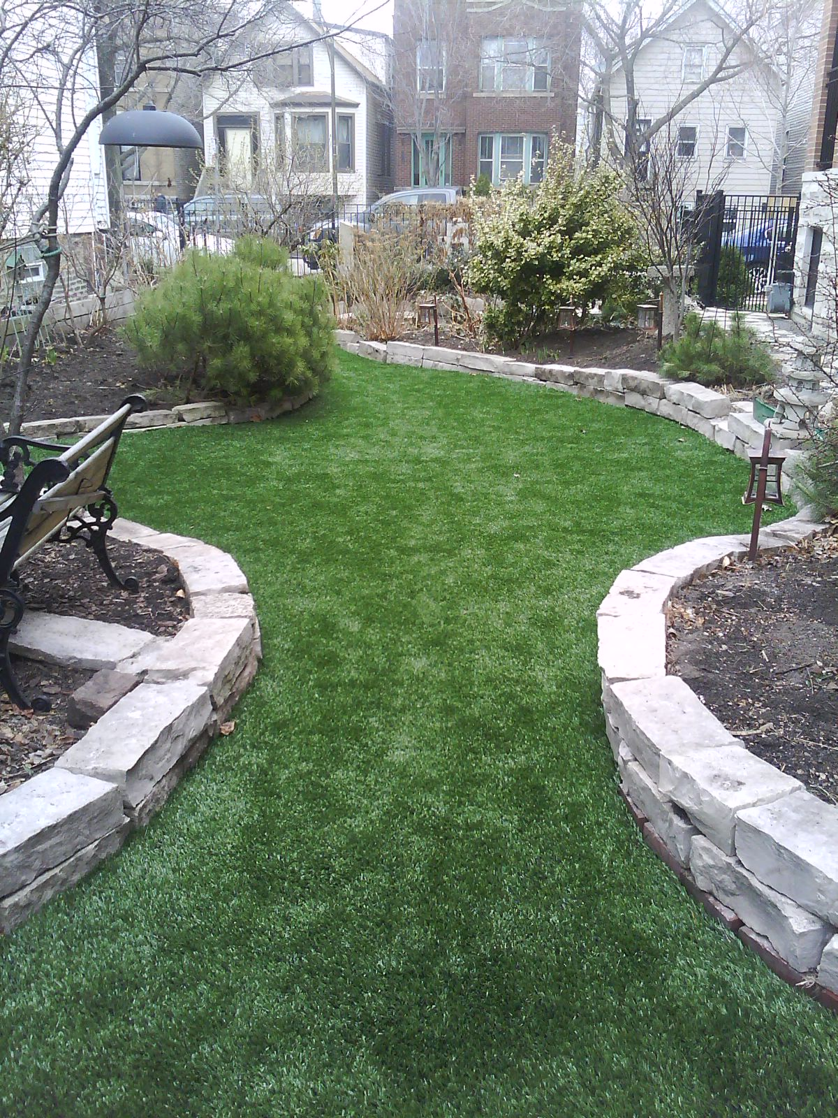 Backyard artificial grass installation in Chicago with stone retainer walls