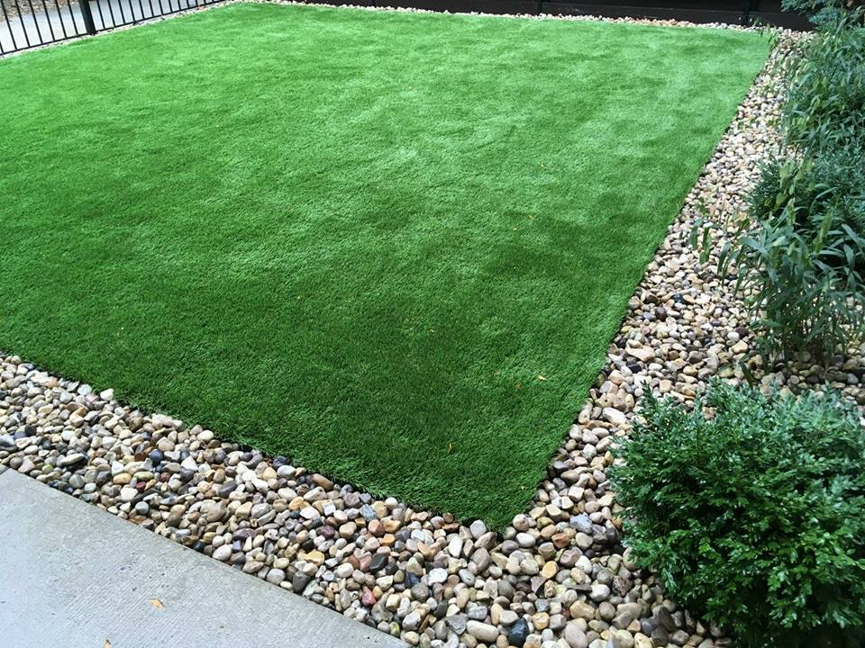 Artificial turf lawn installation in Chicago with river rock edging
